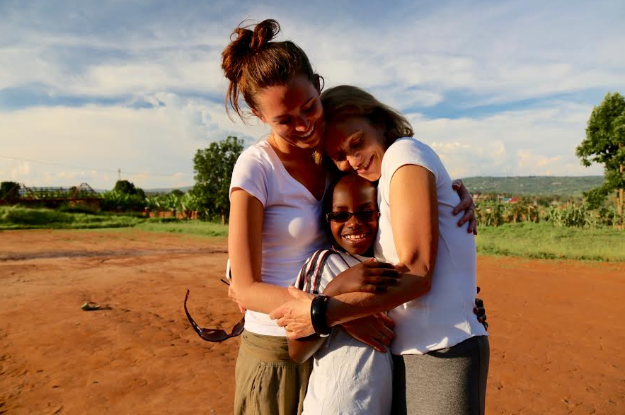 Aimable receiving a hug from his sponsors, Hannah and Jane (from left to right).